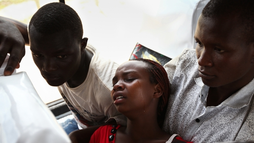 A rescued student (C) is overcome by grief as she waits to be transported home from Garissa town