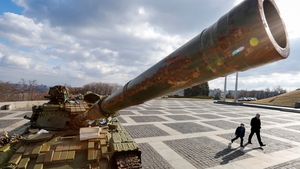 A man and boy pass a tank said to have been seized from separatist rebels in the armed conflict in eastern Ukraine