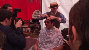 A man has his hair combed to replicate the style of the era