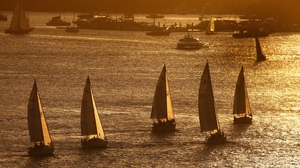Yachts sail in a twilight regatta on Sydney Harbour