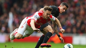 Aaron Ramsey of Arsenal battles for the ball with Philippe Coutinho of Liverpool during the Barclays Premier League match between Arsenal and Liverpool at Emirates Stadium