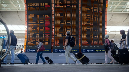 Passengers pass a flight information board at Charles de Gaulle Airport in Paris