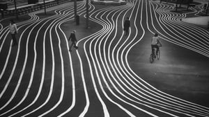 The photo captures twisting white lines on a pavement as four people walk upon it