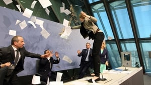 The protester threw paper and glitter at Mario Draghi before being taken away by security