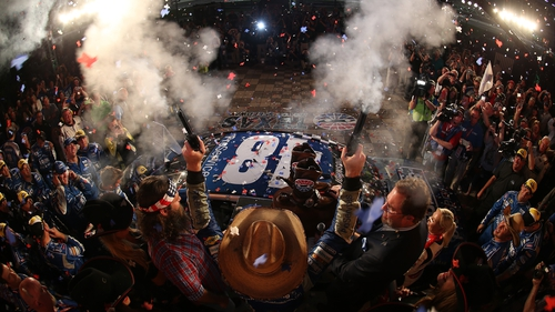 Jimmie Johnson, driver of the #48 Lowe's Pro Services Chevrolet, celebrates with commemorative pistols after winning the NASCAR Sprint Cup Series Duck Commander 500 at Texas Motor Speedway