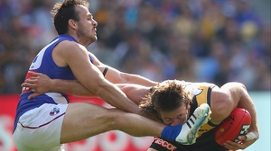 Ivan Maric of the Tigers takes a kick to the nose from Tory Dickson of the Bulldogs during AFL match at Melbourne Cricket Ground