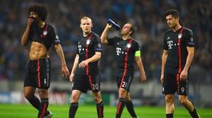 Sebastian Rode, Philipp Lahm and Robert Lewandowski of Bayern Muenchen look dejected in defeat