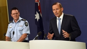 Tony Abbot (R) speaks at a press conference following the arrests