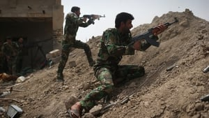 Volunteers from the Shia Badr Brigade militia fire on IS fighters on the frontline in Ebrahim Ben Ali, Anbar