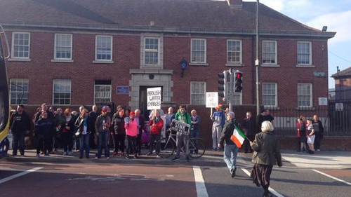 A group has gathered outside Sundrive Road Garda Station