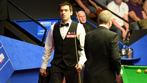 Ronnie O'Sullivan talks with referee Brendan Moore about shoes after he played in his socks against Craig Steadman, during the Betfred World Championships at the Crucible Theatre, Sheffield on Tuesday