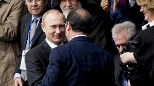 Russian President Vladimir Putin greets Francois Hollande at the centenary commemoration in Yerevan