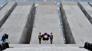 A camerman looks on as soldiers stand guard in front of the Tsitsernakaberd Memorial n