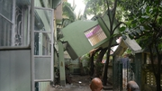 Bystanders look at a collapsed house  in Siliguri, India, following the earthquake