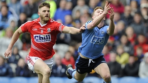 Dublin's Ciaran Kilkenny scores a point despite the attentions of Cork's Eoin Cadogan in the Allianz Football League Division 1 final...