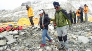 A woman (C) who was injured in the avalanche is tended to by a fellow at the Mount Everest base camp
