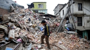 A man surveys the rubble of damaged building a day after a massive earthquake, in Kathmamdu