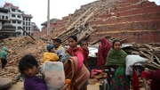Nepalese residents walk beside buildings severely damaged in the earthquake