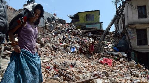 A woman walks past a damaged house in Balaju in Kathmandu