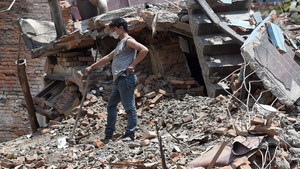 A man clears debris from his damaged house in the capital city, Kathmandu