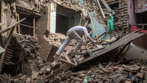 A man climbs on top of debris after buildings collapsed in Bhaktapur