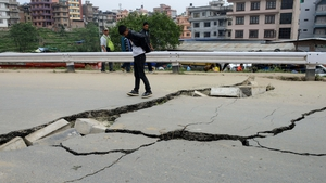 Residents inspect damage caused to a road in Kathmandu