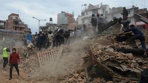 People work to clear rubble in Kathmandu's historic Durbar Square in the aftermath of the quake