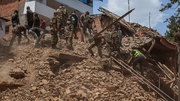 Rescue workers sift through the rubble of a collapsed building in Kathmandu