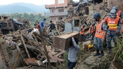 People carry their belongings amidst the rubble of collapsed houses in Bhaktapur, on the outskirts of Kathmandu