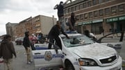 Young men climb on a destroyed Baltimore police car during yesterday's violent protests