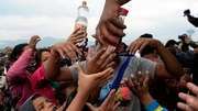 Water is distributed to Nepalese people at a camp set up in the wake of the earthquake