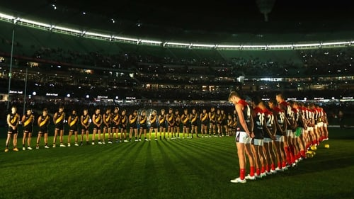 The Tigers and Demons stand for a minute's silence for Anzac Day during their round four AFL match at Melbourne Cricket Ground