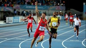 Ryan Bailey crosses the line ahead of Usain Bolt