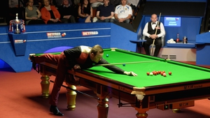 Shaun Murphy takes a shot as Stuart Bingham watches on, with the World Championship trophy in the backround