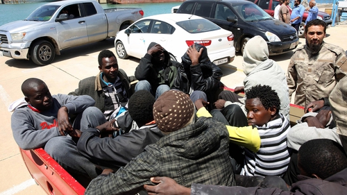 Migrants are held in a pick up truck at the Port of Tripoli after the Libyan coastguard intercepted their boat