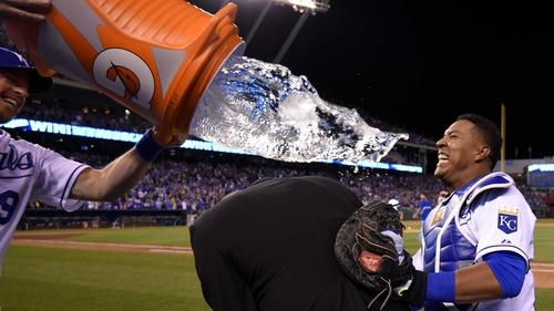 Salvador Perez of the Kansas City Royals uses broadcaster Joel Goldberg as a buffer as team-mate Erik Kratz attempts to douse him with water