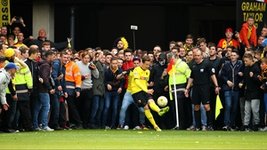 Watford's Daniel Tozser takes a last-minute corner at Vicarage Road as fans wait to invade the pitch as the Hornets secure promotion to the Barclays Premier League
