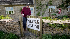 A voter enters a polling station in the Old Post Office in the village of Brokenborough in Wiltshire, England