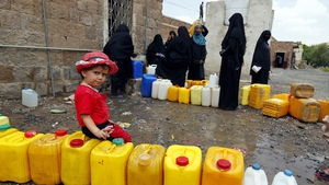 People wait to fill water cans from a clean source