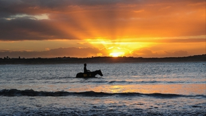 Horse and jockey at sunrise during a Warrnambool trackwork session at Lady Bay, Australia