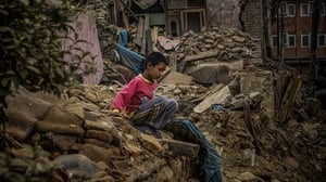A boy plays on a collapsed house in  Kathmandu
