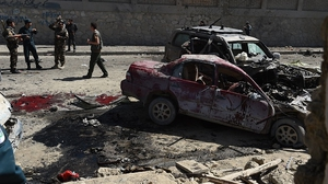 Afghan and foreign security forces inspect the site of the suicide attack in Kabul