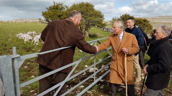 Prince Charles shakes hands with local farmer Oliver Nagle with his father Pat (R) looking on during his visit to the Burren, Co Clare