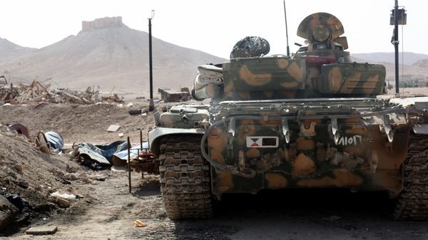 A Syrian armoured tank takes up position during fighting against IS in Palmyra