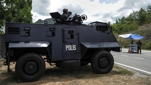 A Malaysian policeman mans an armoured vehicle a day after the government announced the discovery of camps and graves