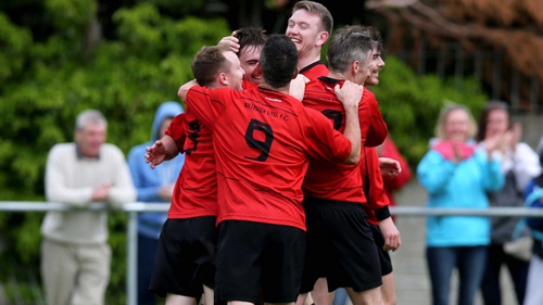 Dylan O'Driscoll of Killester celebrates with team-mates after scoring his side's third goal