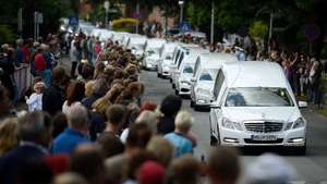 Students from the Joseph-Koenig-Gymnasium high school watch as hearses carrying the remains of 16 of their fellow students and two teachers drive slowly past