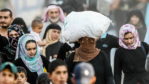 Syrian refugees walk to cross into Turkey at Akcakale border gate