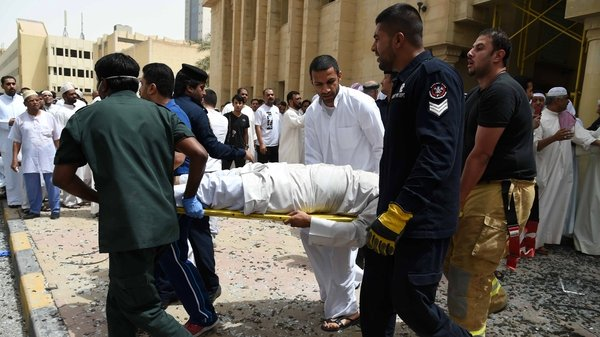 Medical staff carry a man on a stretcher at the site of the attack in Kuwait