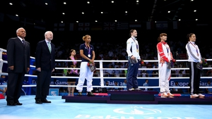 Katie Taylor stands to attention for Amhrán na bhFiann as Olympic Council of Ireland, and European Games, president Pat Hickey (second left) looks on